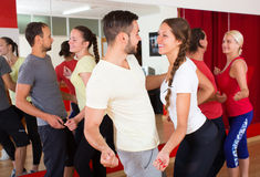 Young adults dancing in a studio. Happy smiling young adults having dance class at studio. Selective focus Royalty Free Stock Photos