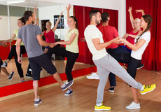 Young adults dancing in a studio. Smiling young adults having dance class at studio. Selective focus Stock Photos