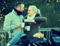 Young adults drinking coffee. Portrait of young adults drinking coffee and chatting near motorcycle outdoor Royalty Free Stock Photos