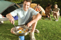 Young adults eating fried breakfast beside tents, focus on man with spatula cooking on camping stove, portrait (tilt) Royalty Free Stock Photography