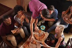 Young adults eating pizzas at a party at home, elevated view Stock Image