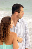 Young adults facing each other looking to the side. A well dressed young couple facing each other, looking to the right, the ocen is in the background Royalty Free Stock Photos