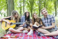 Young adults have fun with guitar. At the campground Stock Photo