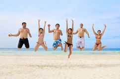 Young Adults Having Fun at the Beach. Six attractive and fun-loving young adults having fun at the beach. Jumping with excitement while on vacation together Royalty Free Stock Photography