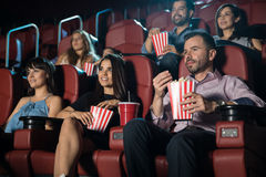 Young adults at the movie theater. Small audience of young adults watching a movie and eating snacks at the cinema theater Royalty Free Stock Images
