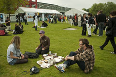 Young Adults Picnicking in Park, Paris, France. Celebration of the World Fair Trade Day by having a giant, open to all, picnic on the Lawn at La Villette Park Royalty Free Stock Image