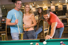 Young adults playing pool in a bar.  Royalty Free Stock Photography