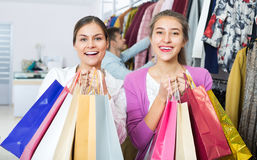 Young adults with purchases in shop. Happy smiling young adults holding bags with purchases in apparel shop Stock Photo