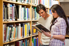 Young adults reading a book. In a library Stock Photography