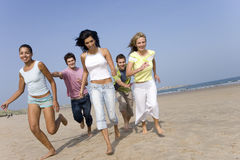 Young adults running on beach Royalty Free Stock Photos