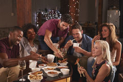 Young adults sharing a Chinese take-away at a party at home Royalty Free Stock Photo