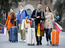 Young adults in shopping tour. Portrait of happy young adults friends chasing streets in shopping tour Stock Images