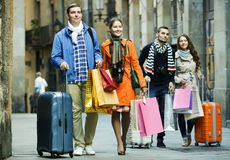 Young adults in shopping tour. Portrait of happy young friends chasing streets in shopping tour Royalty Free Stock Photo