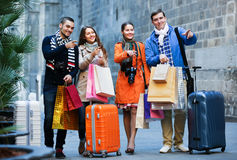 Young adults in shopping tour. Portrait of positive young adults friends chasing streets in shopping tour Royalty Free Stock Image