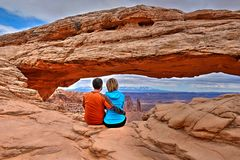Young adults sitting and hugging by arch. Mesa Arch in Canyonlands National Park. Moab. Cedar City. Utah. United States Royalty Free Stock Photo