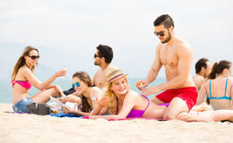 Young adults sunbathing on beach Royalty Free Stock Images