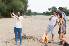 Young Adults Taking Pictures And Selfies On Sandy Beach Stock Photo
