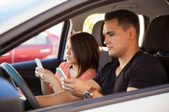 Young adults texting and driving. Portrait of reckless young adults texting on their smartphones and driving, ignoring the road Stock Photo