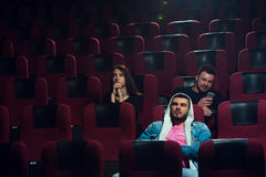 Young adults watching boring film in movie theater. Two friends looking at screen while another one using his smartphone. Cinema, entertainment and leisure Stock Image