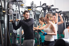 Young adults working out in fitness club Royalty Free Stock Photos