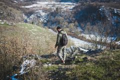Young adventure man standing on top of cliff on the edge of valley in winter. Young man standing on top of cliff in winter mountains with backpack enjoying view Royalty Free Stock Photo