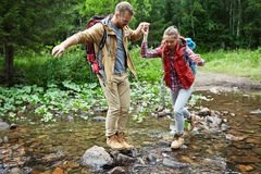 Young adventurers. Hiking lovers walking through river in the forest Royalty Free Stock Photography