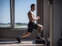 Young aerobics male coach shirtless leaning on step stock photos