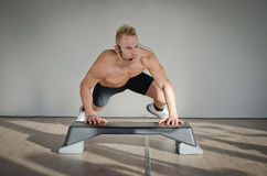 Young aerobics male coach on step teaching class. Young aerobics male coach shirtless leaning on step teaching class Royalty Free Stock Photography
