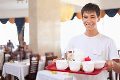 Young affable waiter keeps tray at restauran