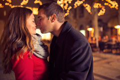 Young affectionate couple kissing tenderly. On Christmas street stock photo