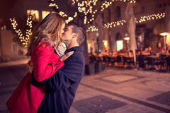 Young affectionate couple kissing tenderly. On Christmas street stock photos