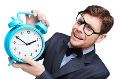 Young afraid man holding alarm clock Royalty Free Stock Photo