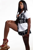 Young African Ameican woman standing foot on stool Stock Photography