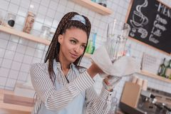 Young african american barista checking a clean glass royalty free stock image