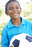 Young African American Boy Holding Football In Park Stock Photo
