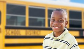 Young African American Boy Near School Bus. Adorable Young African American Boy Near a School Bus stock photography