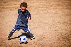 Young African American boy playing soccer. During fall Royalty Free Stock Photo