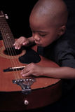 Young African american boy plays the guitar. Young african american boy explores the guitar royalty free stock image