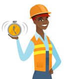 Young african-american builder holding alarm clock Royalty Free Stock Photo
