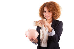 Young african american business woman holding a piggy bank - Afr. Young african american business woman holding a piggy bank, isolated on white background Royalty Free Stock Photography