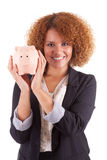 Young african american business woman holding a piggy bank - Afr. Young african american business woman holding a piggy bank, isolated on white background Royalty Free Stock Photos