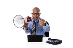 Young African-American businessman, angry. Young attractive African American businessman in office at his desk holding a megaphone and angry clenching one's fist Stock Image