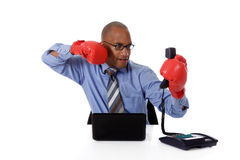 Young African american businessman, angry. Young attractive African american businessman in office, wearing gloves, ready to hit the telephone receiver. Studio Stock Photo