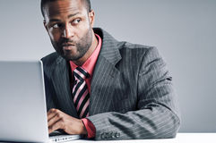 Young African American Businessman Being Sneaky On Laptop Royalty Free Stock Images