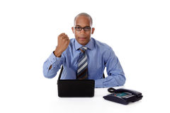 Young African American businessman, clenched fist. Young attractive African American businessman in office sitting against desk with a laptop and telephone Royalty Free Stock Photo