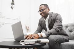 Young African American businessman in a gray suit working behind a laptop. stock photo