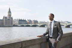 Young African American businessman looking away with hand in pocket Royalty Free Stock Images