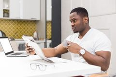 Young African American businessman reading a newspaper at breakfast. stock photos