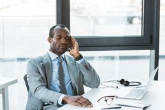 Young african american businessman suffering from headache while sitting. At workplace Stock Photos