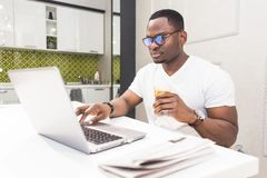 Young African American businessman working on a laptop in the kitchen in a modern interior. stock image